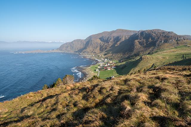 Pohled dolů na pobřeží, kde se nachází kemp Goksøyr inájemní domy. Runde Environmental Centre je až za tím nejvzdálenějším cípem ostrova
